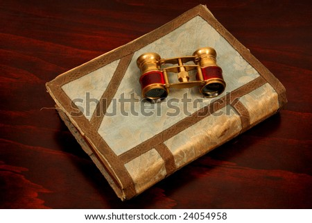 Antique opera glasses on old book on old table top - stock photo