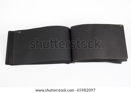 Antique photo album with blank black pages and hand lettered white page numbers. Grunge and wear intact. - stock photo