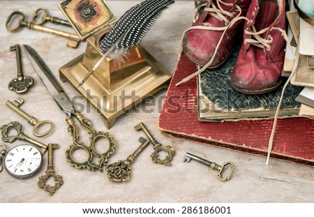 Antique photo albums, keys, office supplies and baby shoes. Nostalgic still life. Selective focus. Retro style toned picture - stock photo