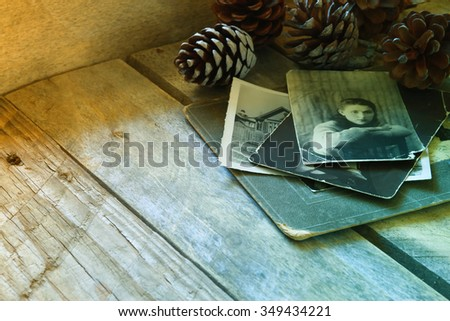 antique photos and old book on wooden table. retro toned and filtered image. selective focus - stock photo