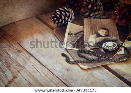antique photos and old locket on wooden table. filtered image. selective focus - stock photo