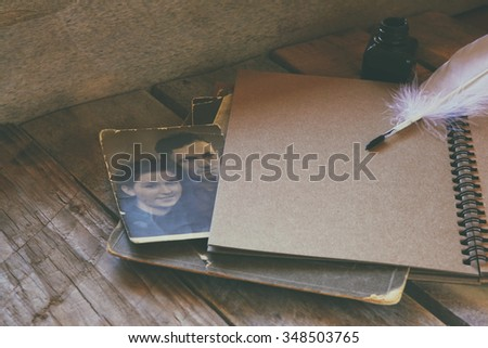 antique photos and old open notebook on wooden table. retro feded and filtered image. selective focus - stock photo
