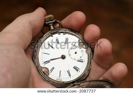 Antique pocket clock in a man hand isolated on orange - stock photo