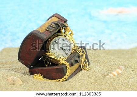 Antique pocket clock in a  treasure chest on a beach - stock photo