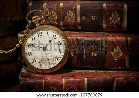 Antique pocket clock over ancient books in Low-key, copy space. Concept of time,the past or deadline. - stock photo