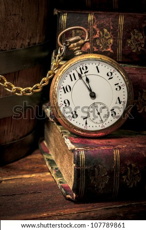Antique pocket clock showing a few minutes to midnight over ancient books in Low-key. Concept of time,the past or deadline. - stock photo