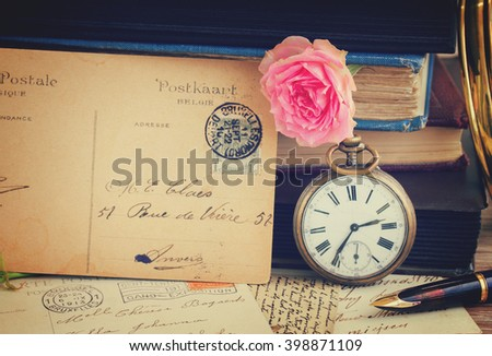 antique pocket  clock with postcard  on vintage  books and letters background, retro toned - stock photo