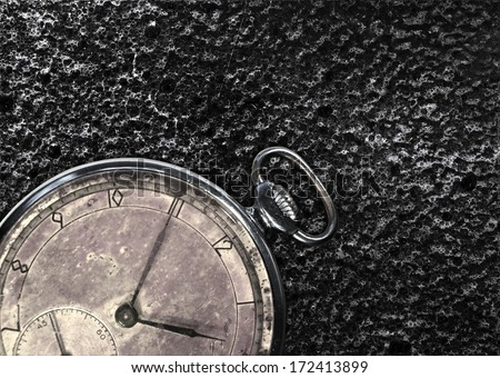 Antique pocket watch on a black grungy background - stock photo