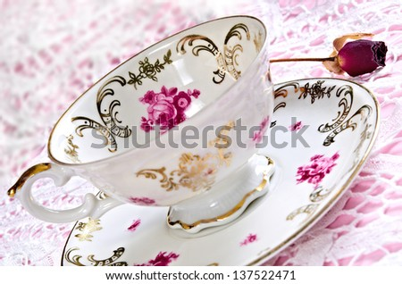 Antique porcelain tea cup on lace table cover - stock photo