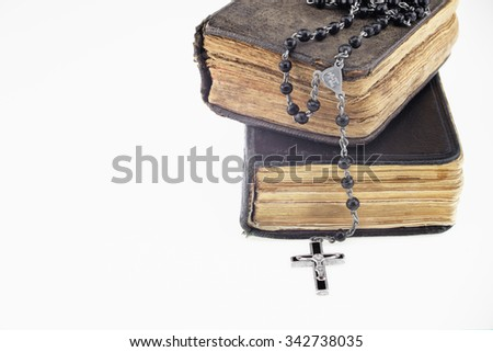 Antique prayer-books and a black rosary on it in a white background - stock photo