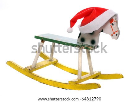 Antique rocking horse with red Santa's cap, wooden toy isolated on white.  Traditional christmas gift. - stock photo