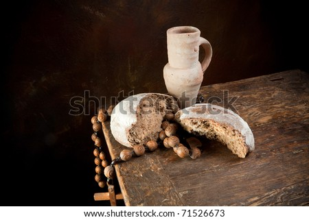 Antique rosary and wine pitcher with a rustic loaf of bread - stock photo