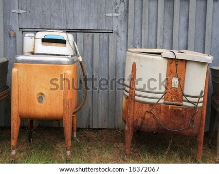 Antique rusted washing machine behind and country shed