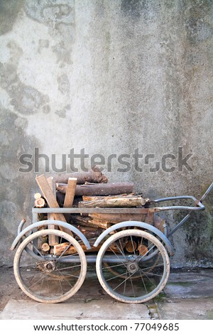 antique rusty wheelbarrow with a load of wood