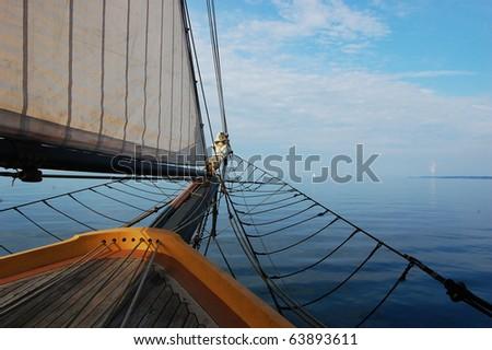 Antique Sailing Ship heading to the sky line - stock photo