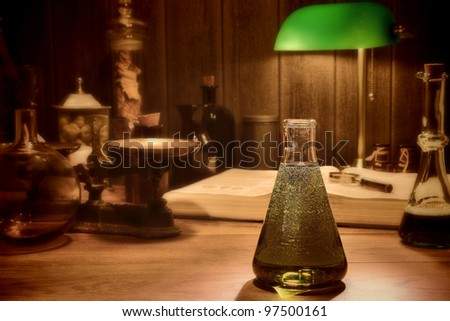 Antique science and chemistry research laboratory with an old conical glass lab Erlenmeyer flask filled with potion and vintage scientific instruments in retro faded colors - stock photo
