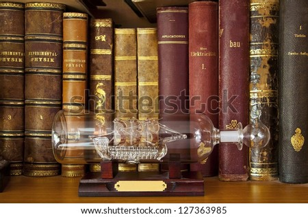 Antique scientific books on a shelf with a glass ship in a bottle
