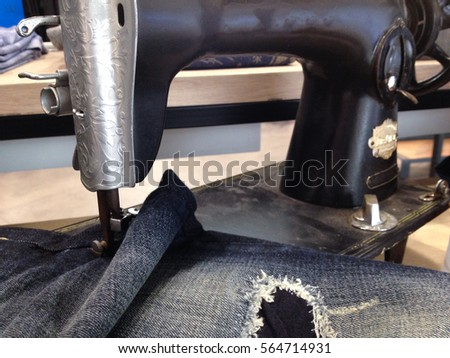 Antique sewing machine and blue jeans fabric