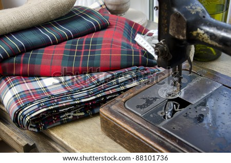 Antique sewing-machine and plaid fabric - stock photo