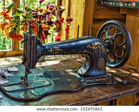 Antique sewing machine in the interior of the ancient Russian hut - stock photo