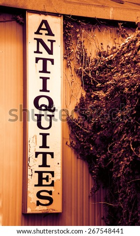Antique shop sign near old wooden garden wall overgrown with a ivy shrub. Toned photo. Vignette. - stock photo