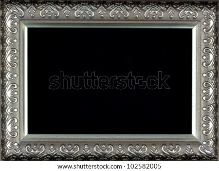 Antique silver and patterned picture frame black background - stock photo