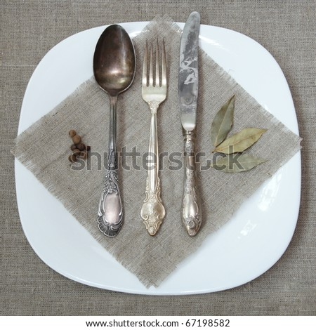 Antique Silver Tableware on Sacking Napkin over Plate - stock photo