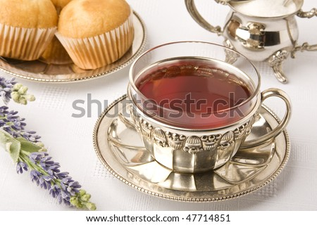 Antique silver tea set. Cup of tea served with fairy cakes. - stock photo