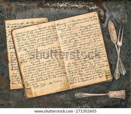 Antique silverware on rustic metal background. Vintage handwritten recipe book. Retro style toned picture - stock photo