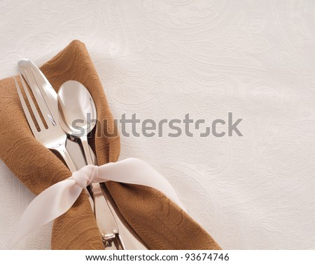 Antique Silverware Place Setting in a Brown Napkin and Tied with a Satin Ribbon against a White Background, a Table Cloth with Room for Text or Copy - stock photo