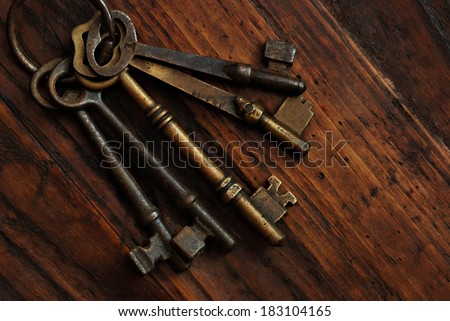 Antique skeleton keys on rustic dark wood background.  Low key still life with directional natural lighting. - stock photo