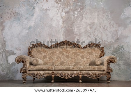Antique sofa against old stucco background - stock photo
