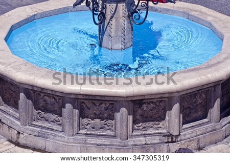 Antique stone fountain with blue water on sunny day, Greece - stock photo