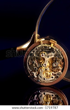 Antique stopwatch and magnifier, reflected on black wood - stock photo