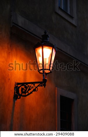 Antique street lamp on a wall. Prague - stock photo