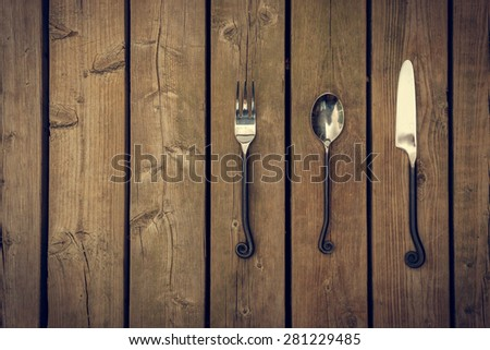 Antique style cutlery, a fork, spoon and knife with twirled, rapier like work metal stems against a natural wooden board background. - stock photo