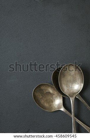Antique style serving spoons on a rustic slate background forming a page border