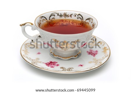 Antique tea cup full of tea on white background - stock photo