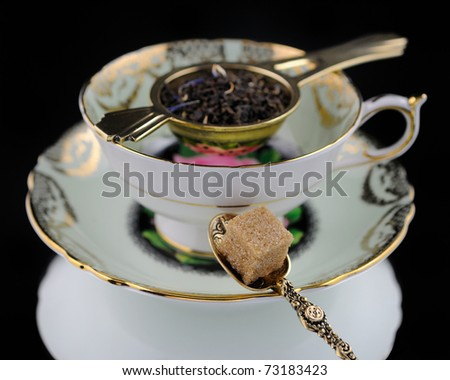 Antique Tea Cup, Spoon & Sugar On Black Background - stock photo