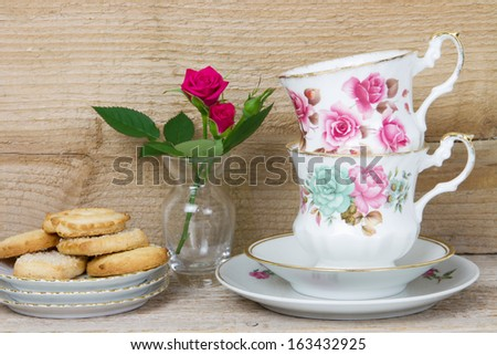 antique teacups, red roses and cookies on a wooden background - stock photo
