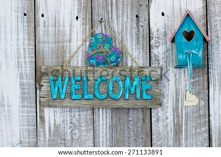 Antique teal blue welcome sign with heart by birdhouse hanging on white painted weathered wood fence - stock photo