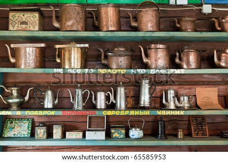 Antique teapots on shelves - stock photo