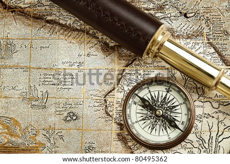 Antique traveling equipment: brass spyglass and compass at old m - stock photo