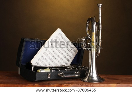 antique trumpet and clarinet in case on wooden table on brown background - stock photo