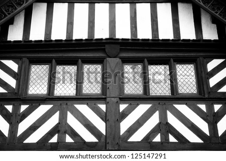 Antique tudor windows surrounded by timber beams. - stock photo