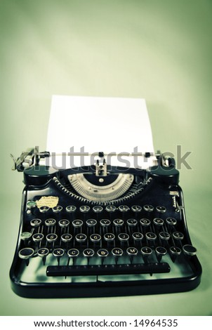 Antique typewriter against a sallow yellow and washed out teal backdrop - stock photo