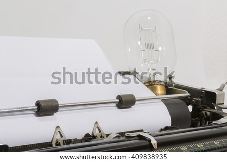 antique typewriter with a light bulb - stock photo