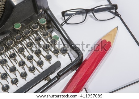 antique typewriter with blank book, reading glasses and a pencil