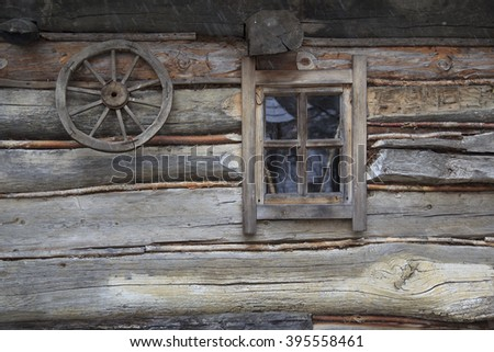 Antique ukrainian rural wooden hut's wall with window and primitive wheel on the wall - stock photo