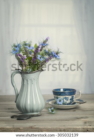 Antique vase of blue cornflowers with vintage tone - stock photo